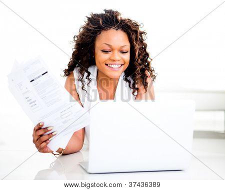 Frau, die Zahlung von Rechnungen online von zu Hause aus und Lächeln