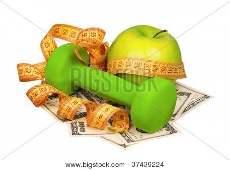 Dumbbells with apple and measure tape on heap of dollars isolated on a white background