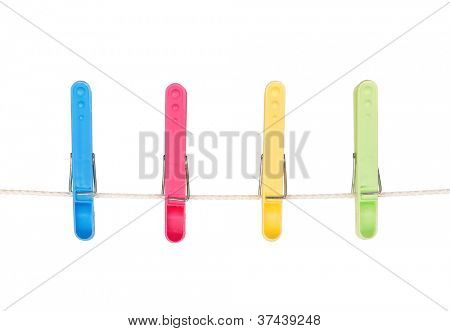 Four colorful clothespins hang on a cord isolated on white background