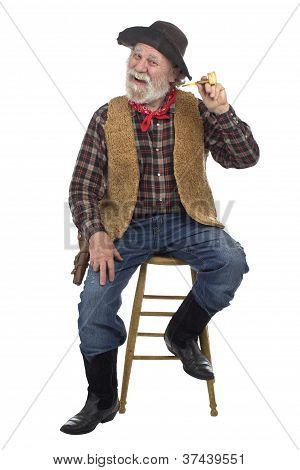 Cheerful Old Cowboy Sits On Stool With Corn Cob Pipe