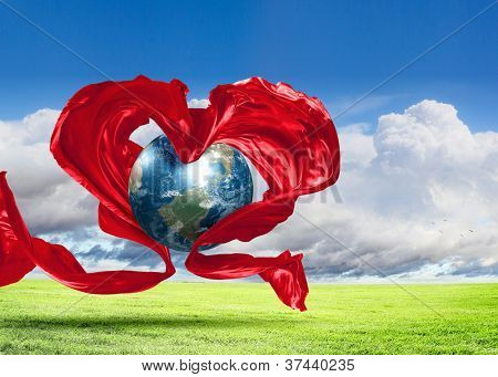 World within the heart symbol on blue sky background.Elements of this image furnished by NASA.