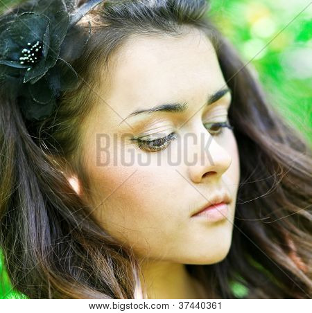 Portrait of beautiful gorgeous young pretty woman relaxing and yearning in spring park, eyes down, long hair and morning pure skin of melancholy face