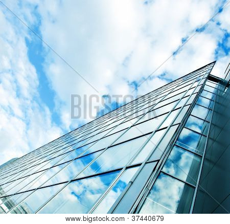 Perspective and underside angle view to textured background of modern glass building skyscrapers over blue cloudy sky