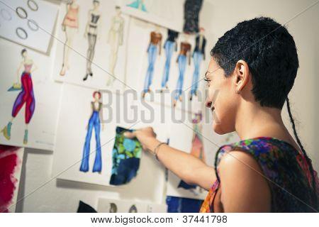 Diseñador de moda femenina contemplando los dibujos de estudio