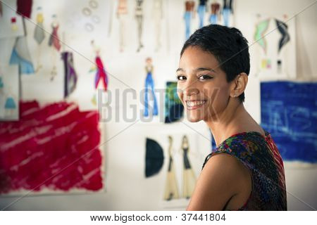 Portrait Of Happy Hispanic Young Woman Working As Fashion Designer