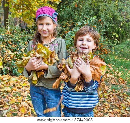 Children in autumn forest play with  fallen down leaf
