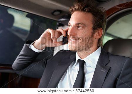 Elegant businessman traveling in luxury car, talking on mobile phone, smiling.