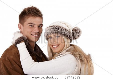 Winter portrait of happy couple smiling in embrace, looking at camera, wearing hat and gloves and coat.