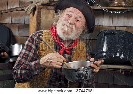 Old Cowboy Stirs Saucepan In Outdoor Kitchen