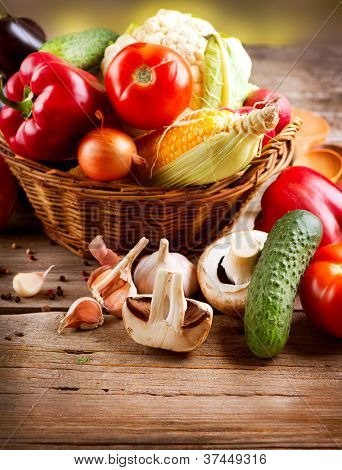 Organic Vegetables in the Basket on a Wooden Background. Healthy Vegetarian Food