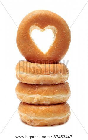 a pile of donuts with a heart shaped hole on a white background