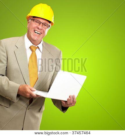 Senior Male Architect Holding Laptop On Green Background