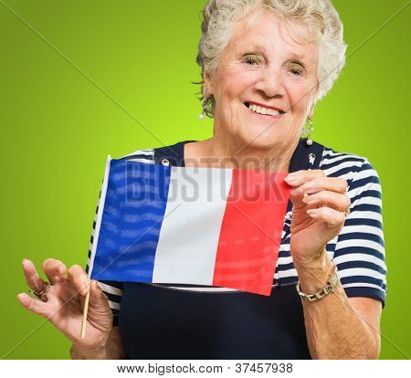 Happy Senior Woman Holding France Flag Isolated On Green Background