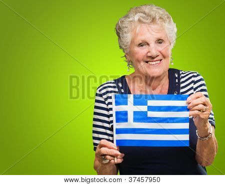 Happy Senior Woman Holding Greece Flag Isolated On Green Background