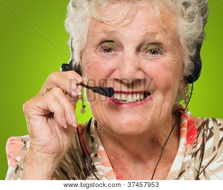 Senior Woman Wearing Headset On Green Background