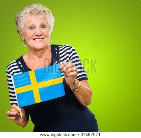 Happy Senior Woman Holding Flag Isolated On Green Background