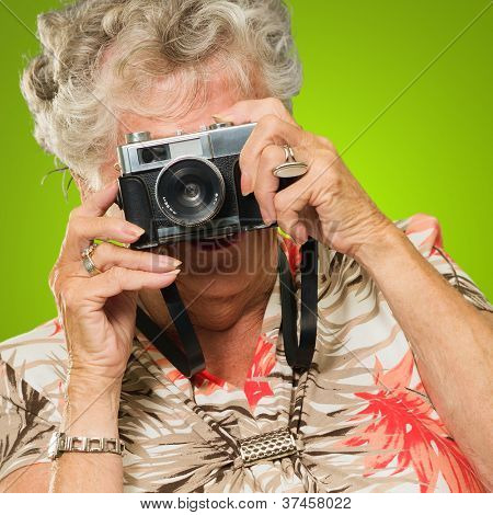 Senior Woman With Old Camera Isolated On Green Background