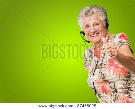 Senior Woman Wearing Headset Showing Thumb Up On Green Background