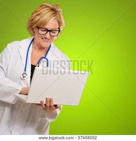 Happy Female Doctor Using Laptop On Green Background