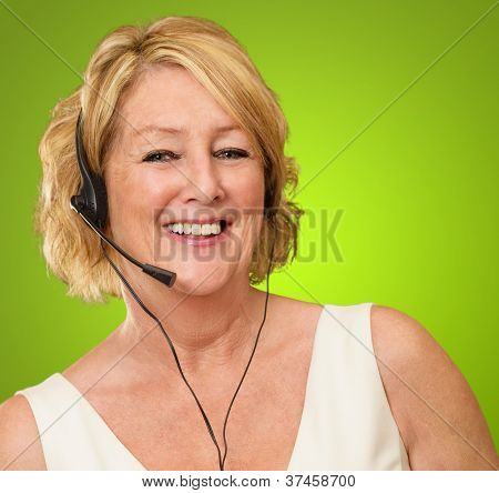 Mature Woman Wearing Headset On Green Background