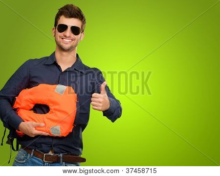 Man Standing Holding Life Jacket Showing Thumbs Up Sign Isolated On Green Background