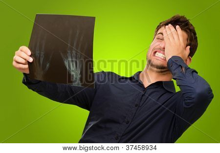 Frustrated Young Man Holding X Ray Isolated On Green Background