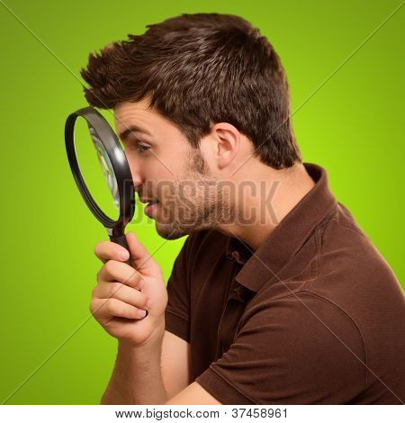 Young Man Holding A Magnifying Glass On Green Background