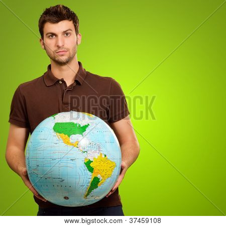 Young Man Holding Globe On Green Background
