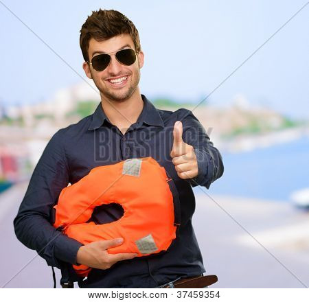 Man Standing Holding Life Jacket Showing Thumbs Up Sign On Beach