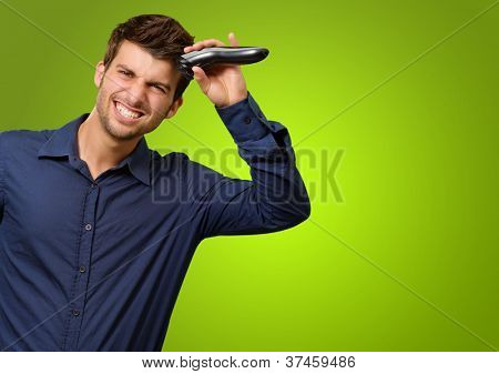 Man Cutting His Hair With Razor On Green Background