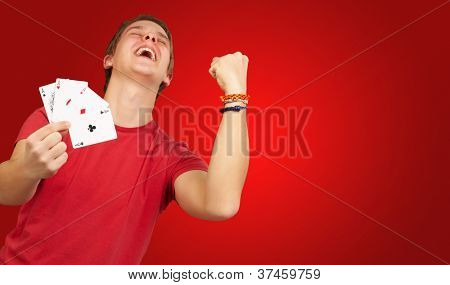 portrait of young man doing a winner gesture playing poker over red
