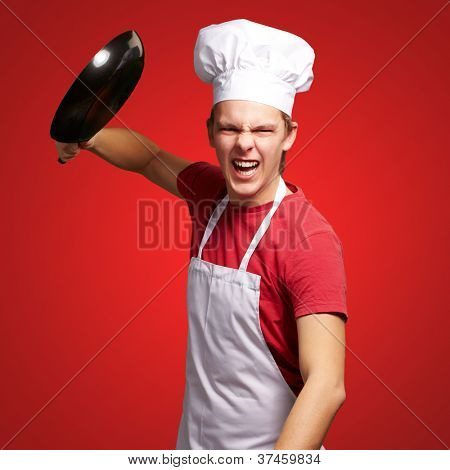 portrait of angry young cook man hitting with pan over red background