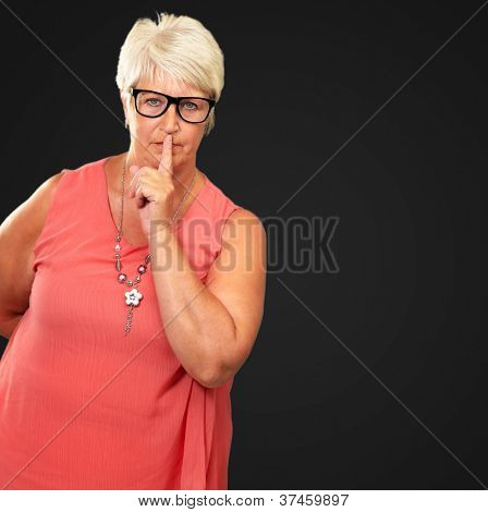 Senior Woman With Finger On Lips Isolated On Black Background
