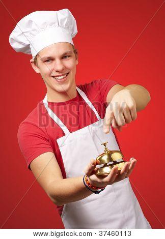 Retrato de hombre joven cocinero presionando una campana de oro sobre fondo rojo
