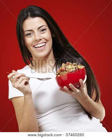woman holding a delicious red breakfast bowl against a red background background