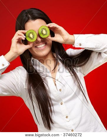 portrait of young girl holding kiwi slices in front of her eyes over red