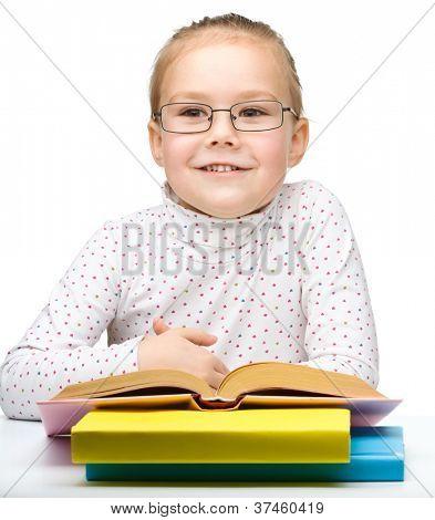 Niedliche fröhliche kleine Mädchen Buch zu lesen, beim Tragen der Brille, isolated over white
