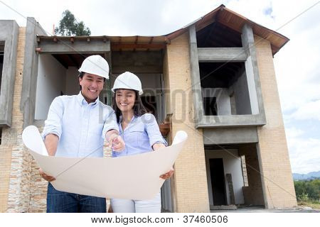 Architects working on a house project and holding blueprints