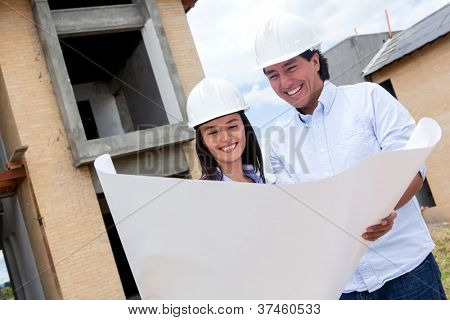 Happy couple building their house and holding blueprints