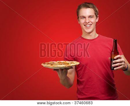 Retrato de hombre joven con pizza y cerveza sobre fondo rojo