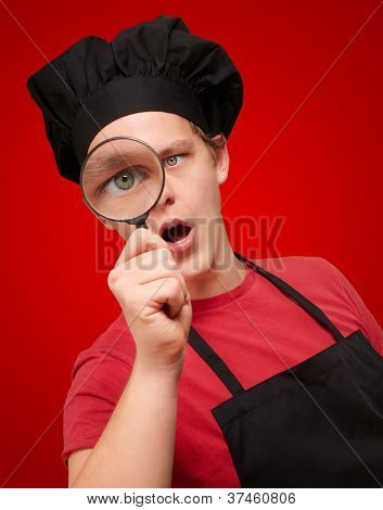 portrait of young cook man looking through a magnifying glass over red