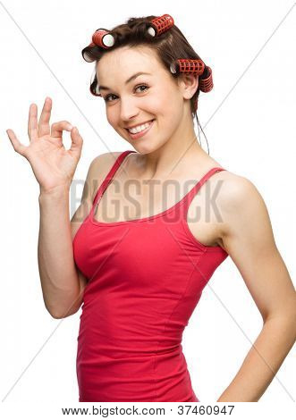 Young woman dressed in red is showing OK sign using both hands while wearing hair-rollers, isolated over white