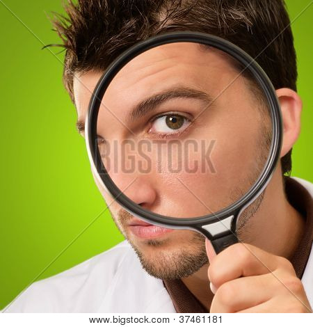 Doctor Looking Through Magnifying Glass On Green Background