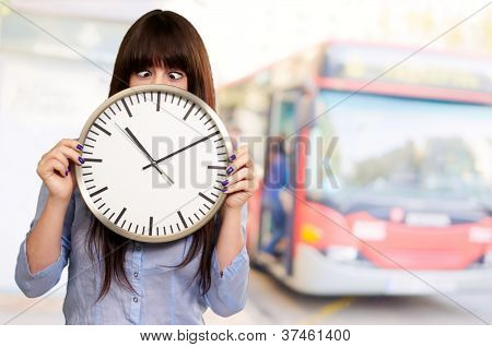 Woman Holding Clock With Squinted Eyes, Outdoor