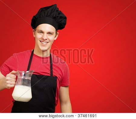 portrait of young cook man holding milk jar over red background