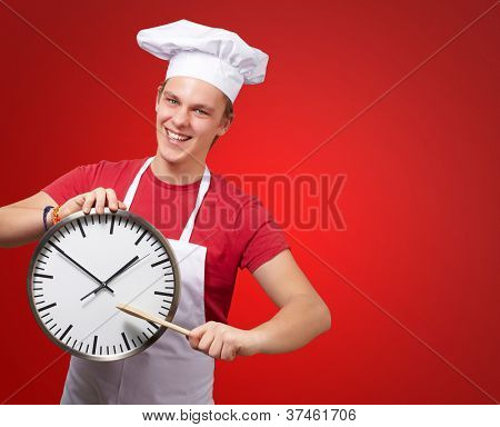 portrait of young cook man pointing a clock over red background