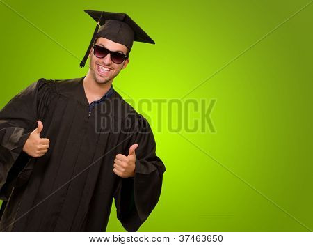 Graduate Man With Thumbs Up Isolated On Green Background