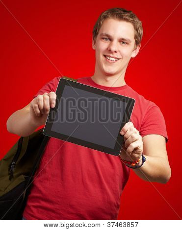 portrait of young man holding a digital tablet over red background