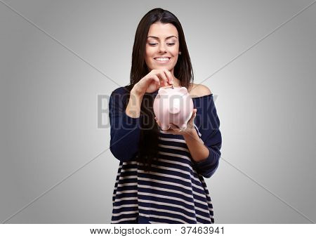 Portrait Of A Young Girl Holding A Piggy Bank On A Gray Background