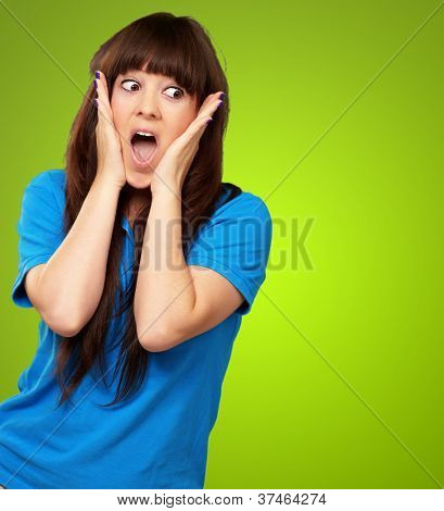 portrait of surprised woman isolated on green background
